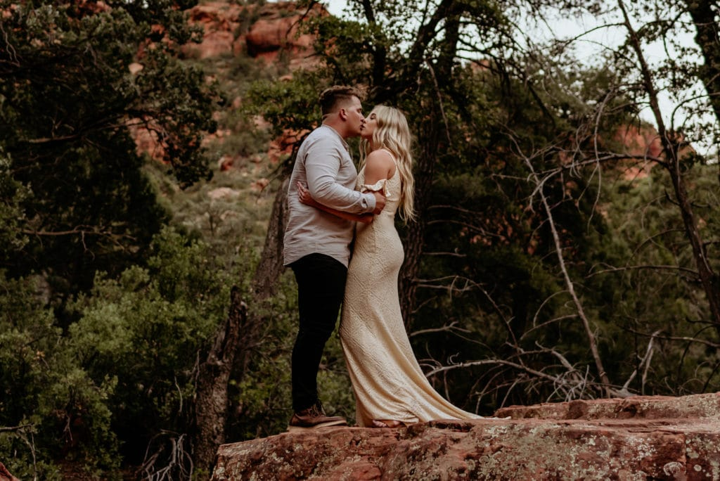 Bride and groom embrace for a kiss in a Sedona red rock canyon during their Sedona Elopement