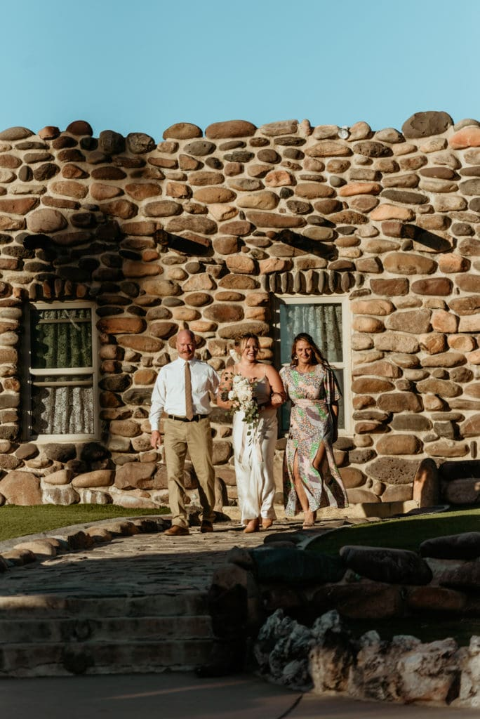 Bride surrounded by her mom and dad walking down the isle during her Wranglers Roost wedding
