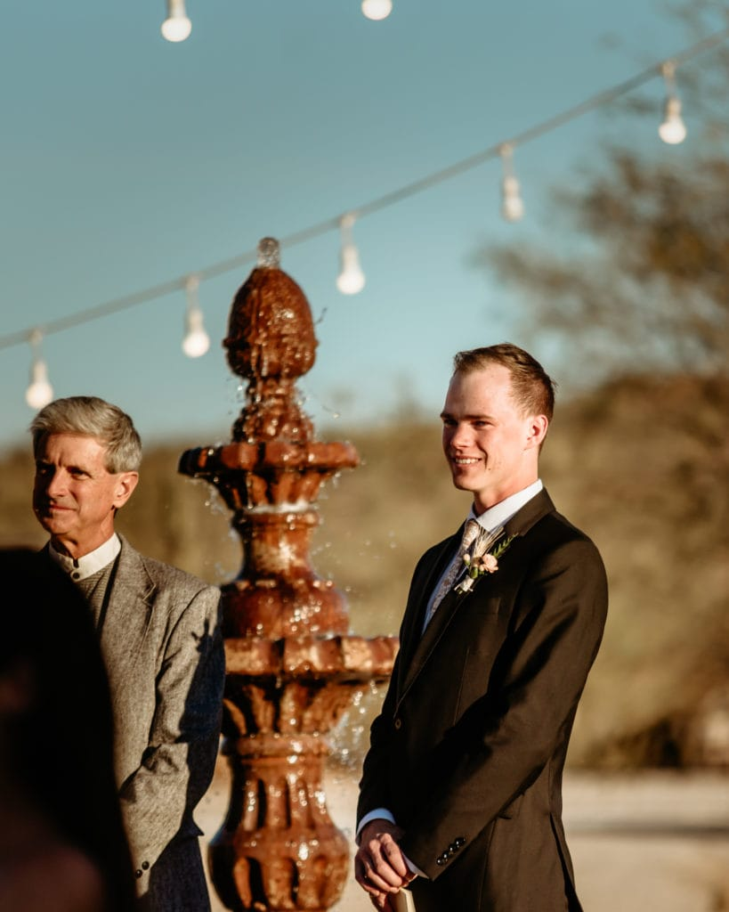 Groom watching bride come down the walkway during their intimate wedding ceremony in the Arizona desert