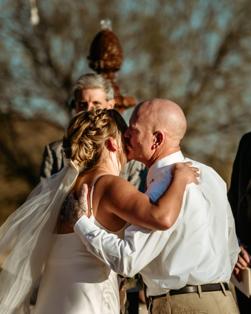 Father kissing bride before intimate wedding ceremony