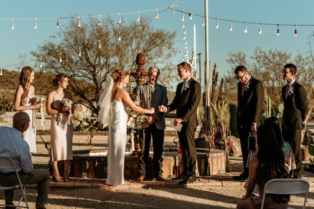 Bride and groom fist bump as part of their imitate Phoenix wedding ceremony