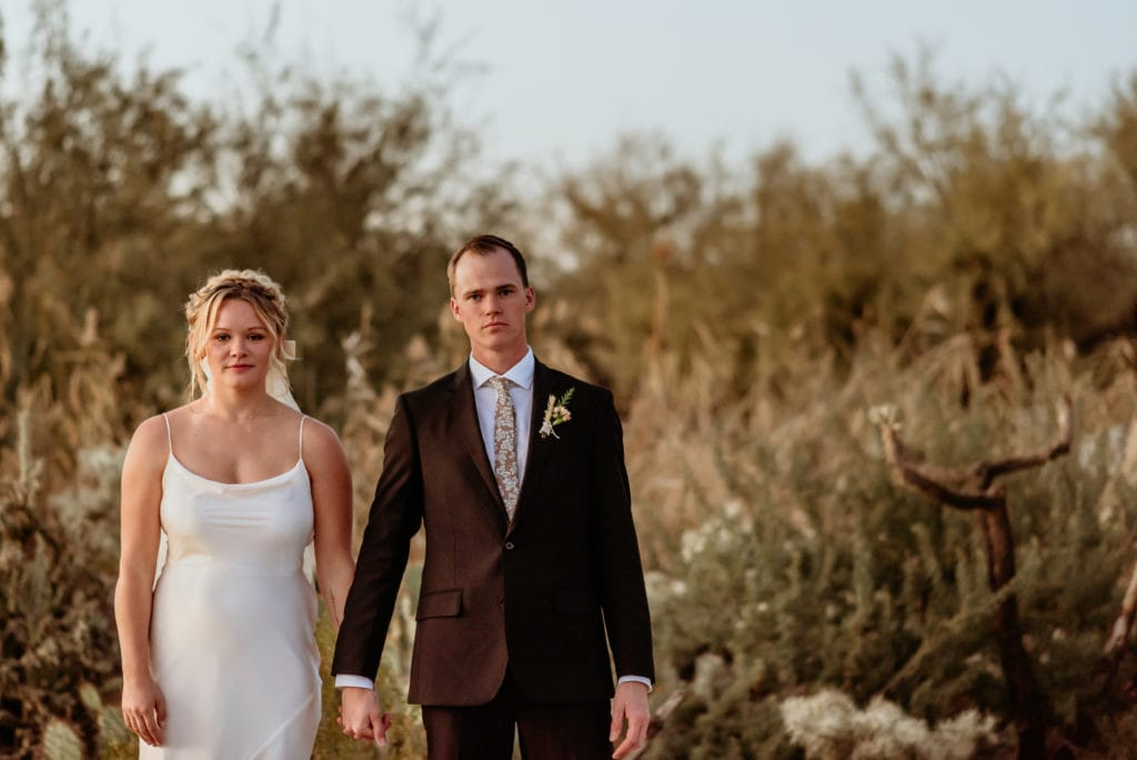 Serious pose as the sun sets during this desert elopement