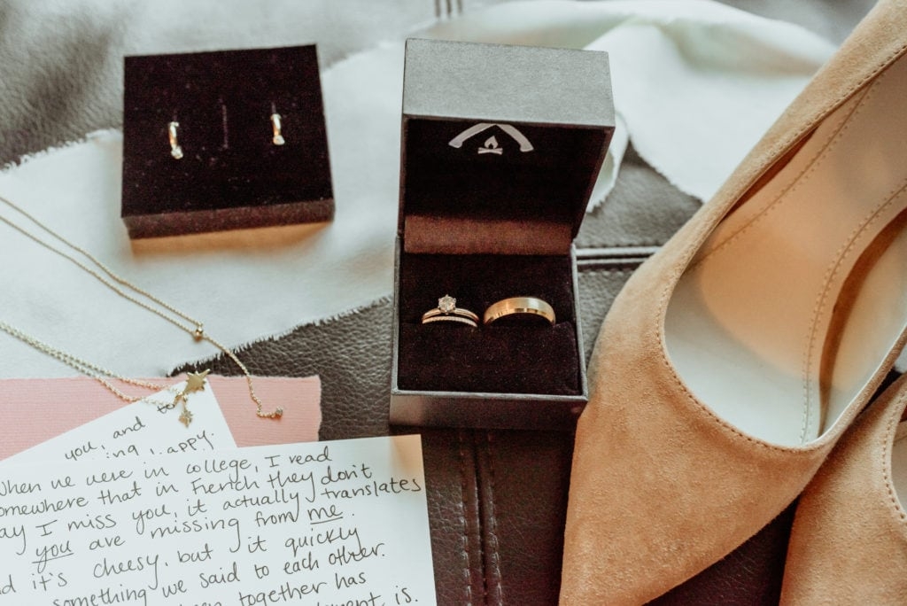 Detail shot with vows, rings, jewelry, and suede shoes