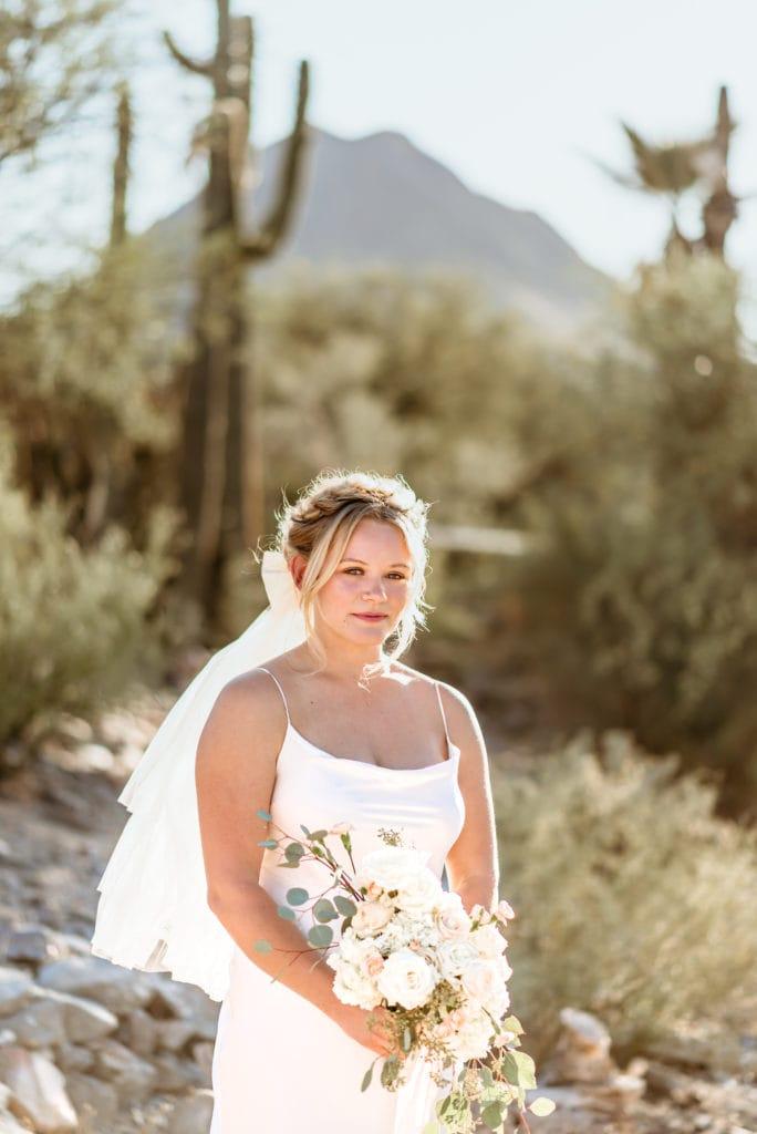 Bride in front of saguaro cacti in the Arizona desert