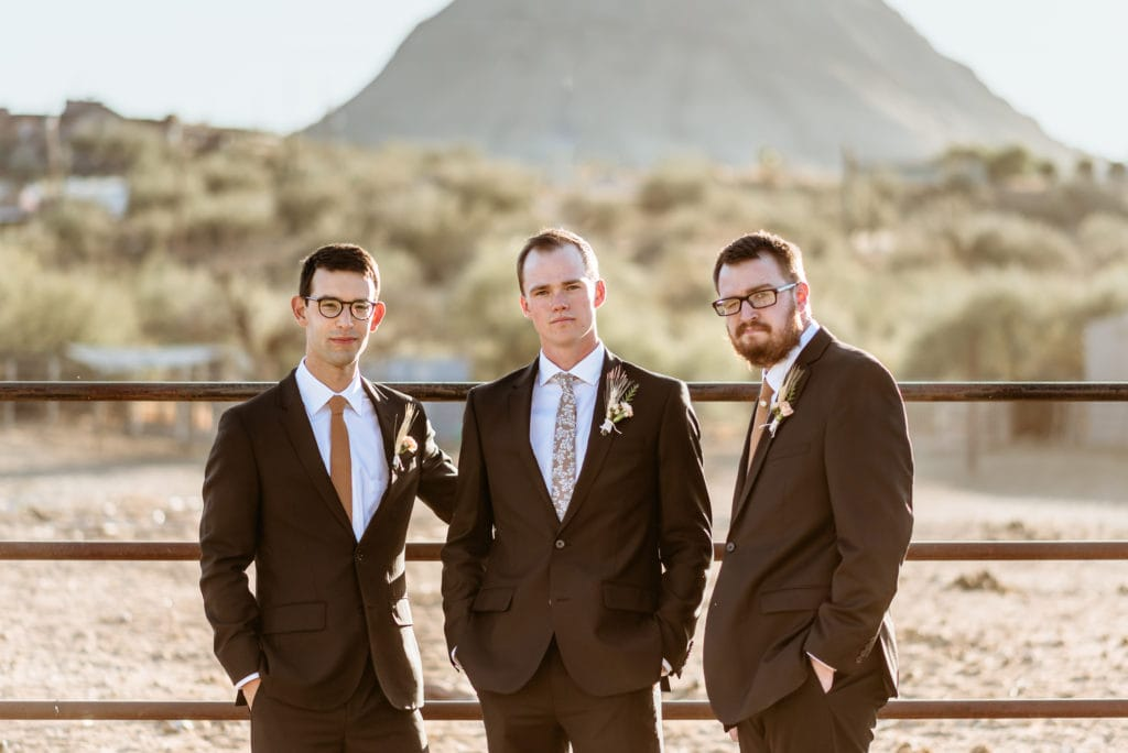 Groom with his brother and best man in front of the horse fence at Wranglers Roost in New River, Arizona