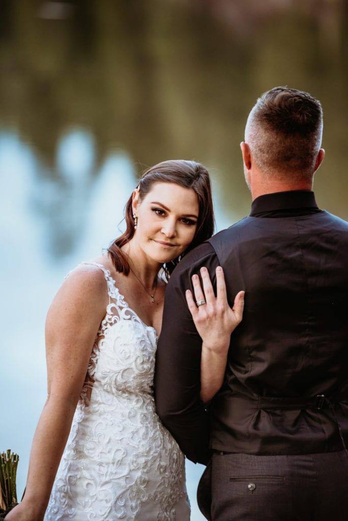 Bride peaking over her new husband's shoulder
