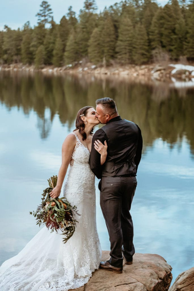 Elopement couple embrace for a kiss framed by the reflection of the tree lined winter lake