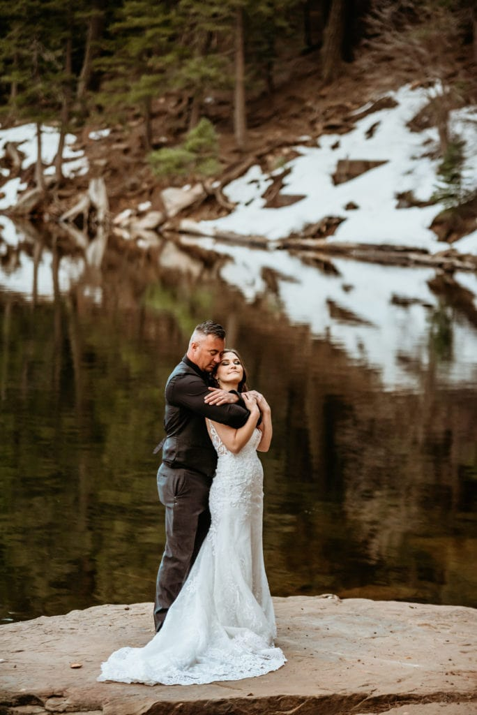 Groom holds his bride tight on the edge of a snow lined lake