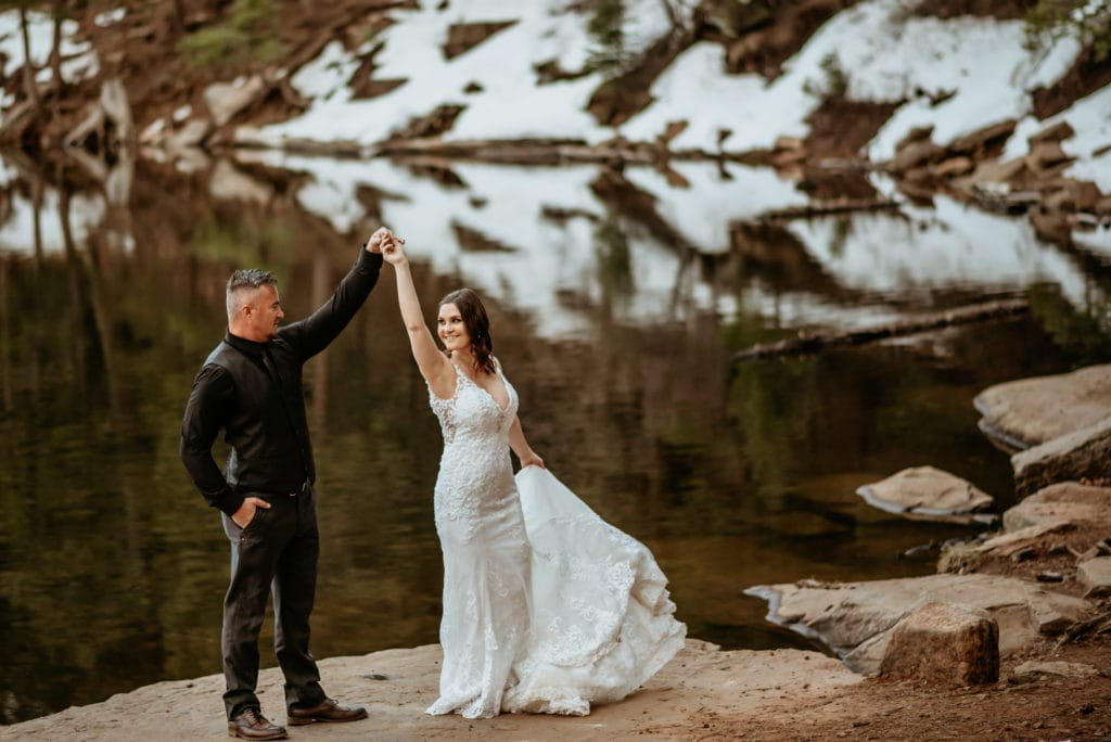 Bride and groom dance at the edge of a snow capped lake in Arizona
