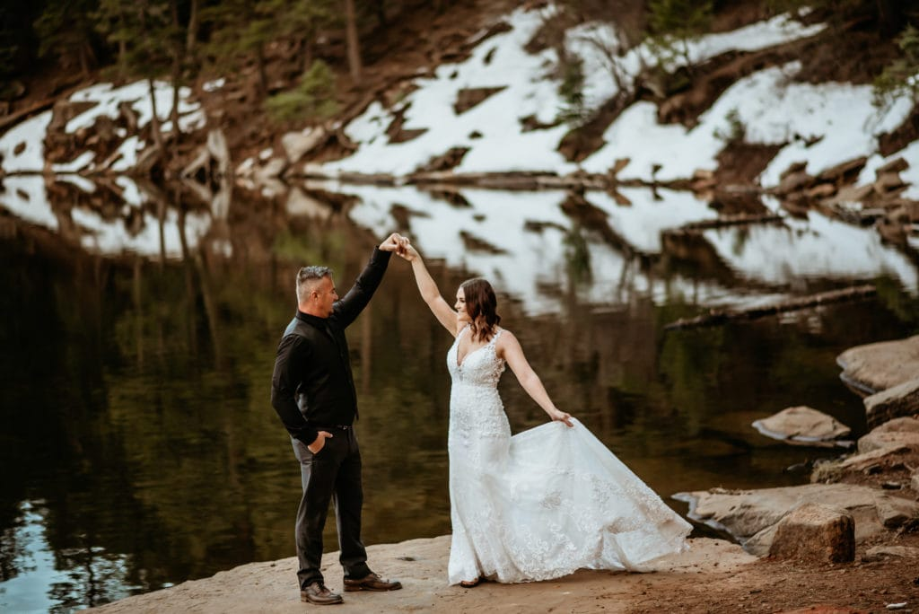 Groom spins his bride as they dance at the edge of a lake