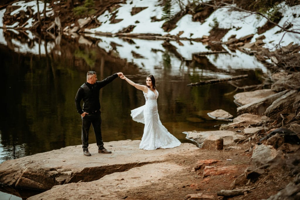 Bride's wedding dress flares out as she dances with her husband at a northern Arizona lake