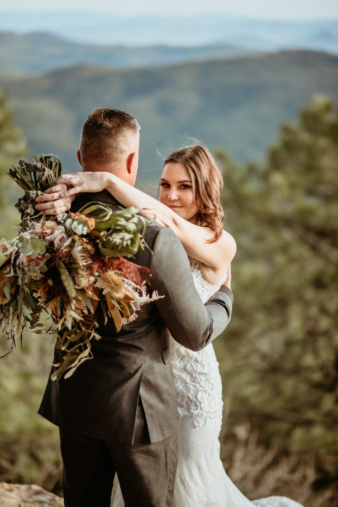 Stunning wildflower bouquet draped over groom's back during northern Arizona elopement