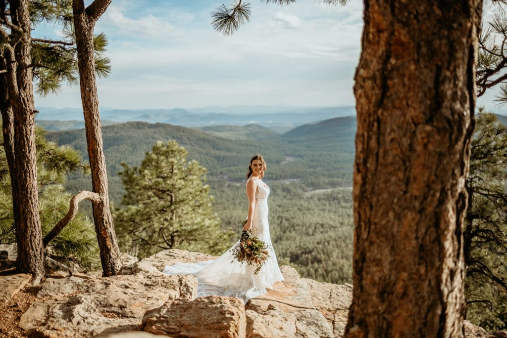 Breathtaking views of trees rolling in the distance as bride stands on ledge of the Mogollon Rim