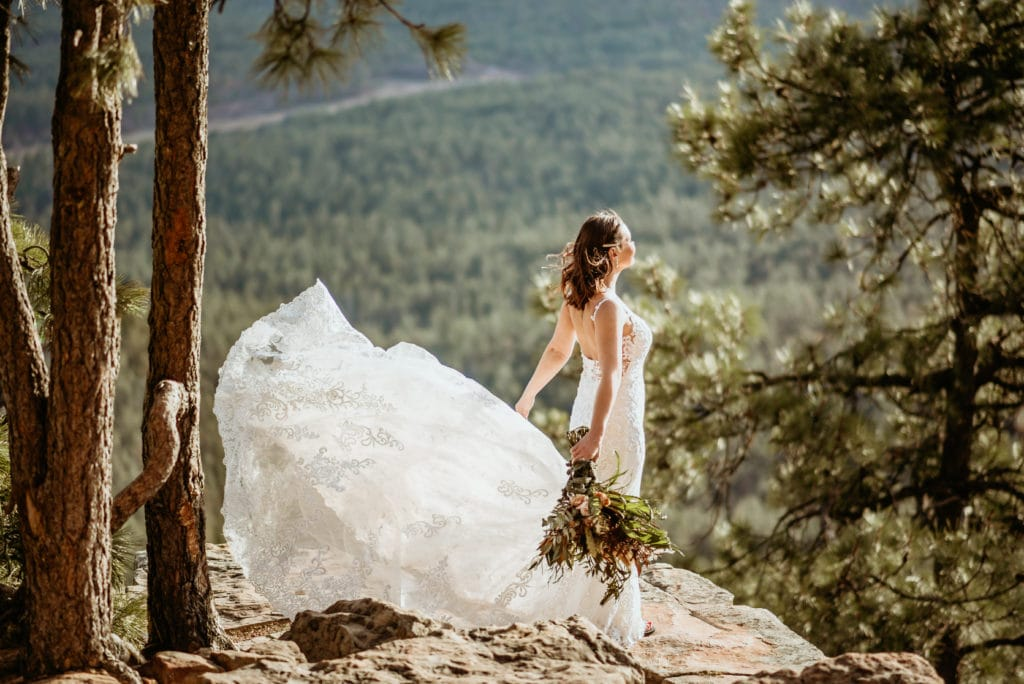 Bride's long wedding dress train blowing in the wind as she stands at the edge of the world on a cliff overlooking the Mogollon Rim