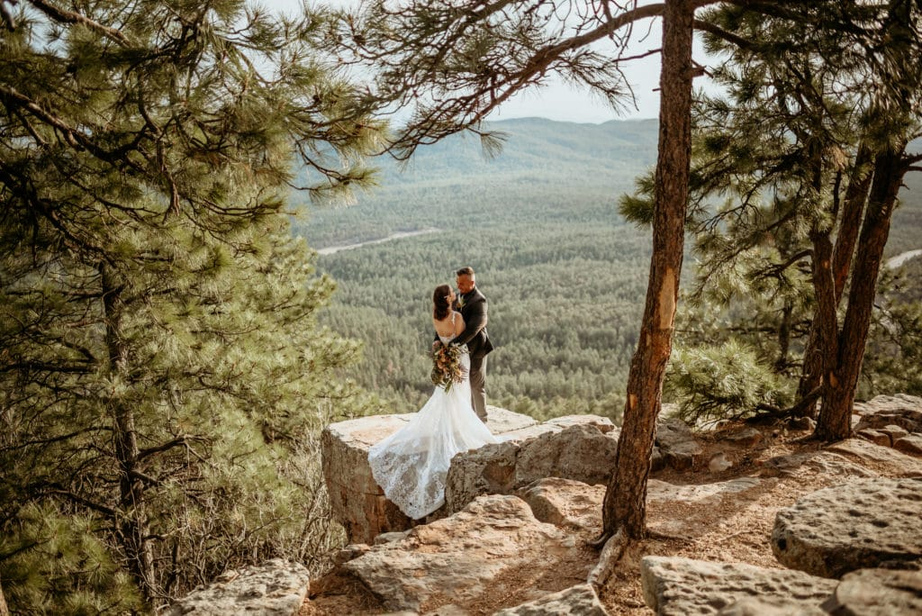 Beautiful elopement couple embracing framed by pine trees in northern Arizona
