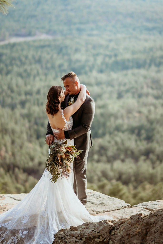 Bride and groom slow dancing as they stand at the edge of the Mogollon Rim in Arizona