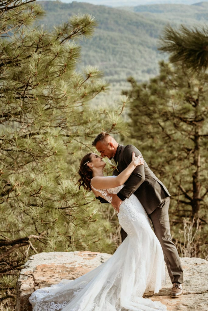 Groom dips his beautiful bride amongst the pines during their intimate elopement