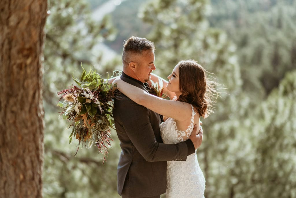Bride looking up into her husband's eyes during their Mogollon Rim Elopement with gorgeous boho boquet