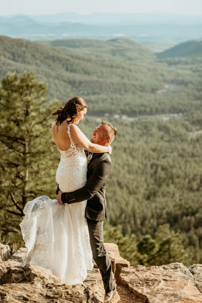 Joyful booty lift as bride smiles at her husband during their gorgeous outdoor wedding