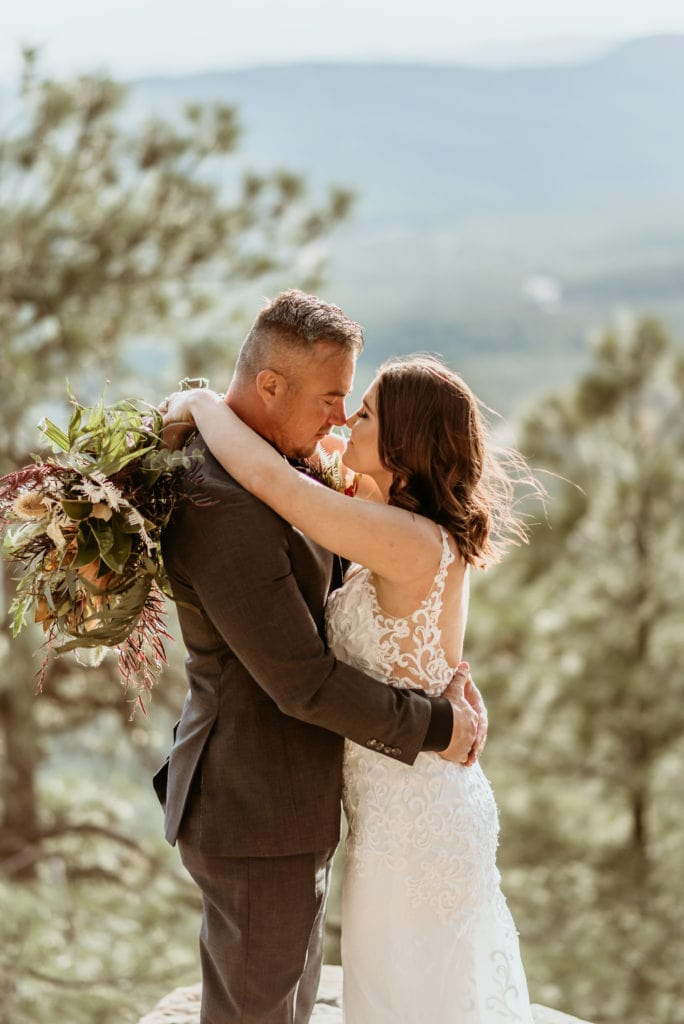 Bride and groom standing on a ledge on the Mogollon Rim