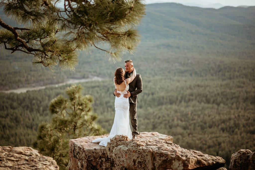 Evergreen as far as the eye can see as an elopement couple stand at the edge of the Mogollon Rim