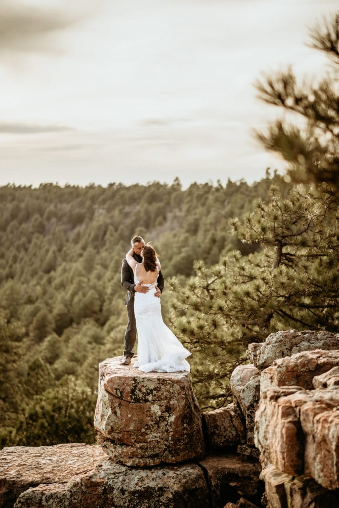 Husband holding his new wife on the edge of the Mogollon Rim during their northern Arizona wedding