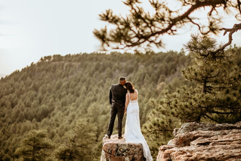 Groom kisses his wife's head as they look off into the distance during their incredible Mogollon Rim wedding