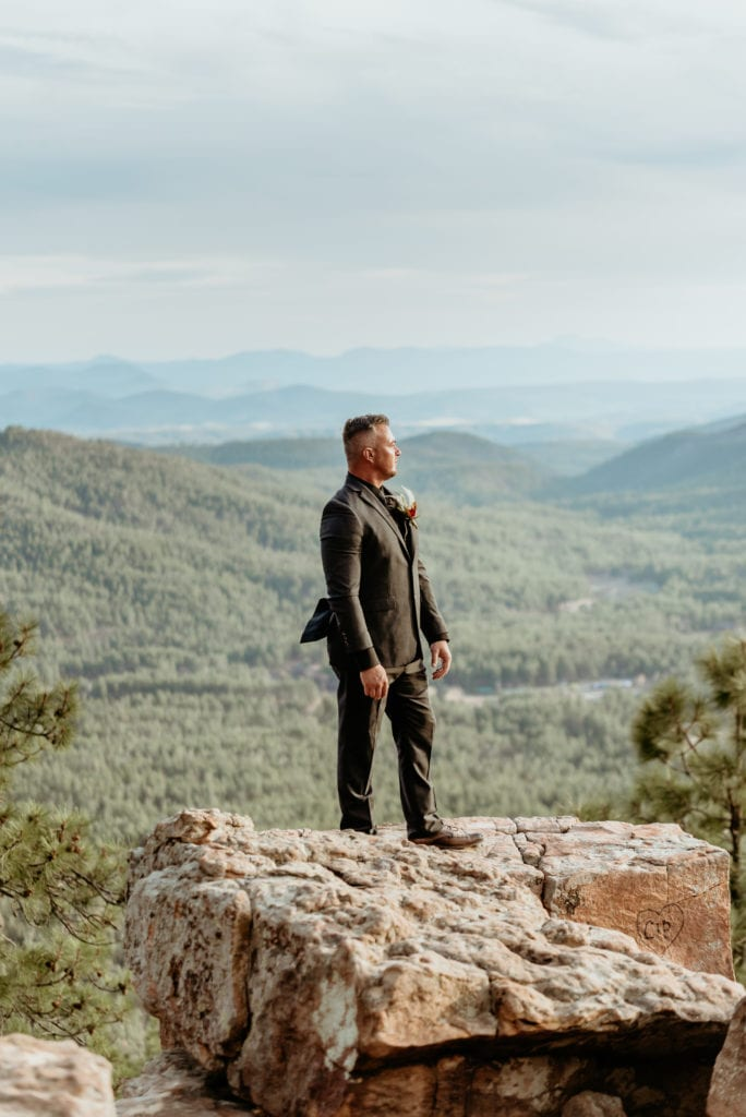 Groom standing in his black suit at the edge of the Mogollon Rim