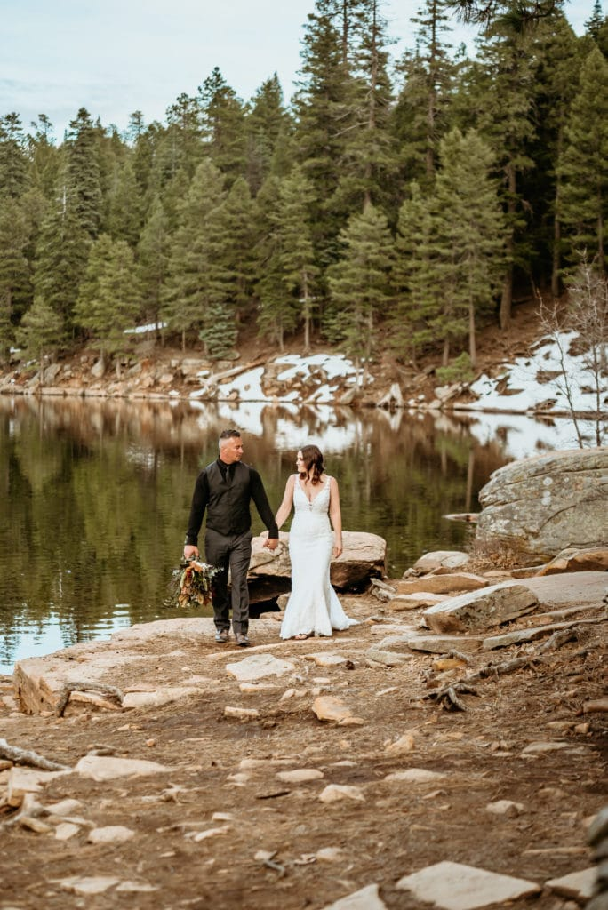 Bride and groom walking hand in hand next to winter lake lined by pine trees and patches of snow