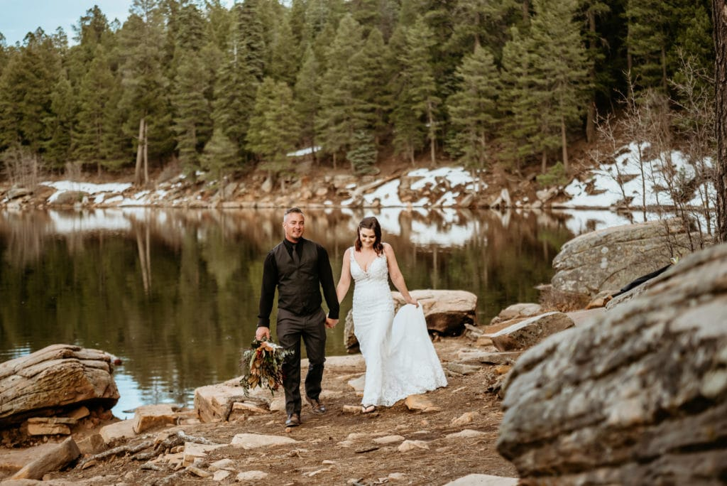 Patches of snow and evergreens line the bank of a wintery lake as bride and groom walk hand in hand