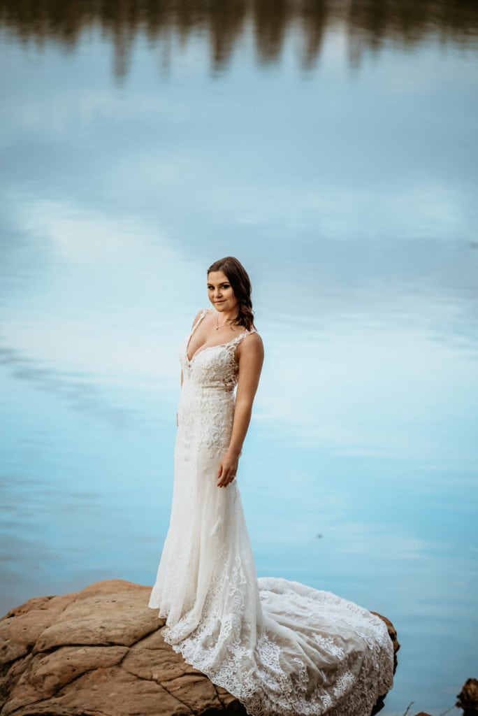 Stunning bride on a stone with light blue sky reflecting in the lake behind her
