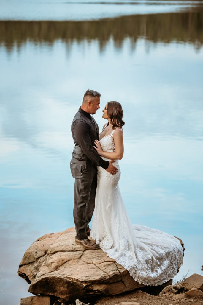 Bride and groom embrace, framed in winter lake reflecting the sky and pine trees
