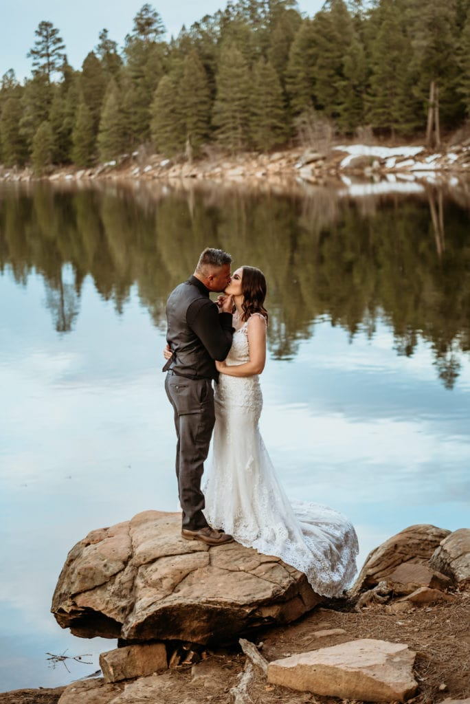 Groom lifts bride's chin as he draws her in for a kiss next to a beautiful winter lake during their Arizona elopement