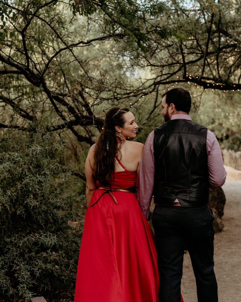 Bride looking over her shoulder as she and groom walk through tree lined trail in her vibrant red wedding dress