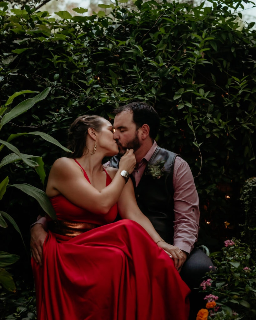 Wedding couple kissing on the bench in one of the courtyards during their intimate Tucson Botanical Gardens Wedding