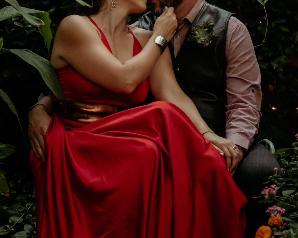 Bride draws grooms chin in for a kiss wearing her vibrant red sating wedding dress with copper belt