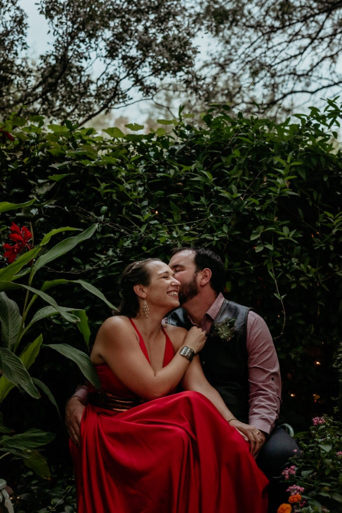 Bride n bright red dress laughing as groom whispers in her ear surrounded by dark green vines at botanical gardens