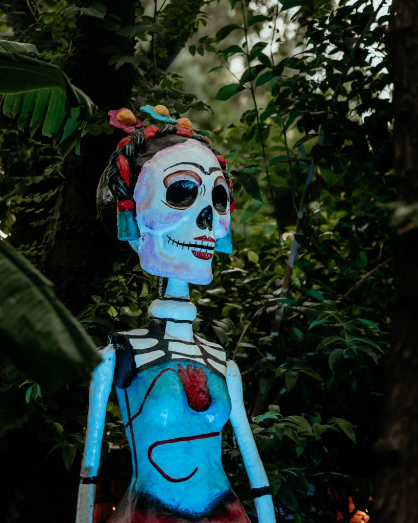 Intricate blue, red and white Dia De Los Muertos sculpture surrounded by jungle vines at the Tucson Desert Botanical Gardens