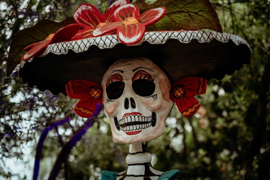 Beautiful Dia De Los Muertos sculpture with bright red flowers at the Tucson Botanical Gardens art exhibit