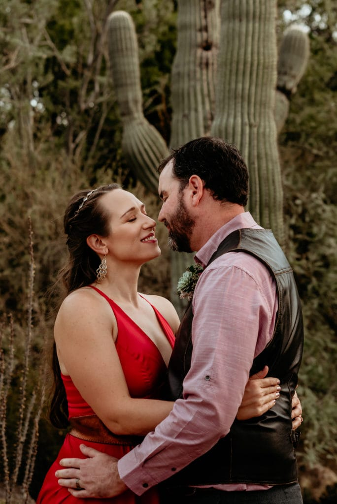 Intimate moment between bride and groom in front of saguaro cactus at the Botanical Garden