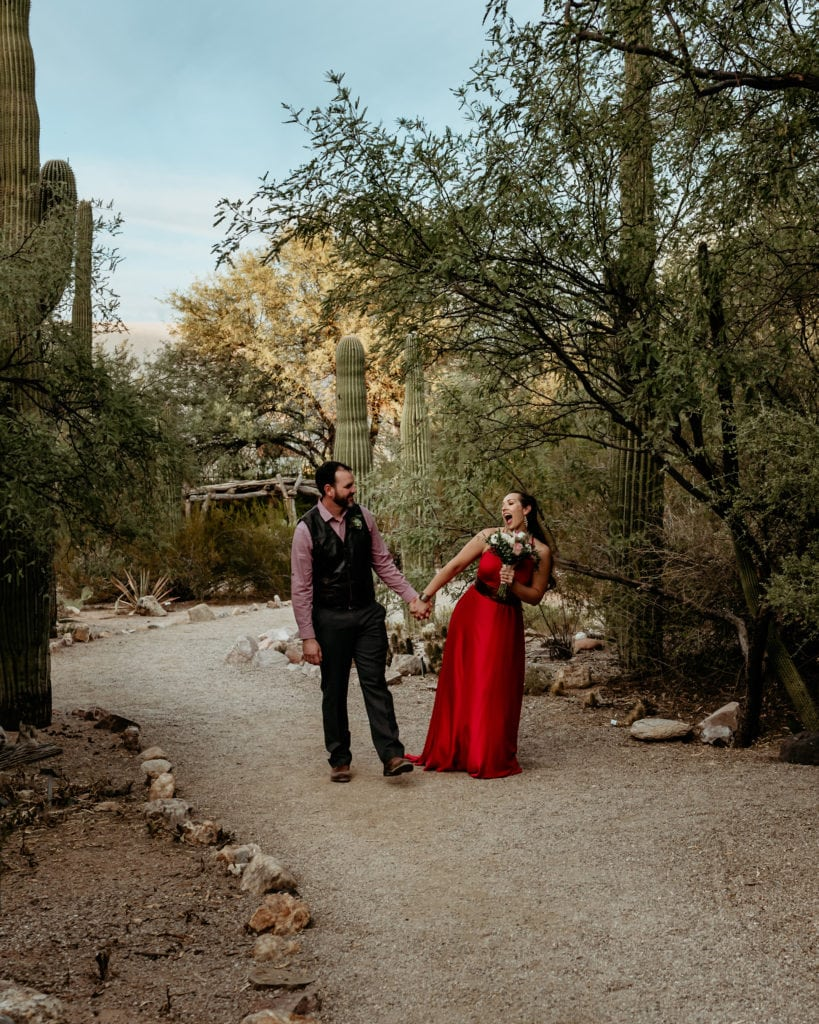 Bride and groom walk hand in hand through the desert landscape at the Tucson Botanical Garden