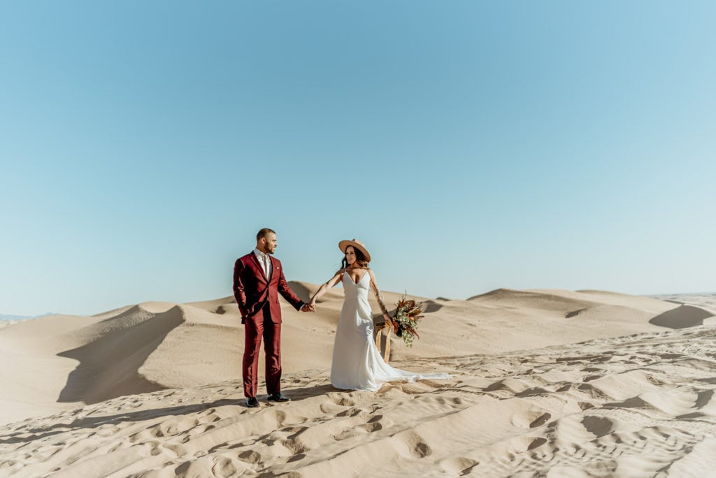 Bride and Groom standing in the desolate desert, surrounded by heaping mounds of golden sand