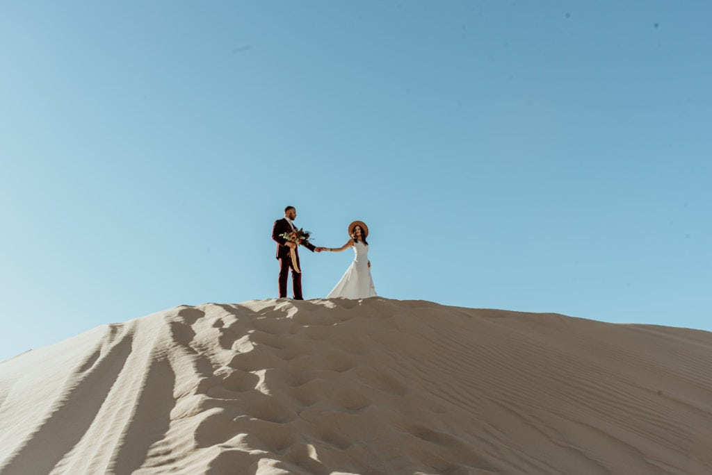 Bride leading groom across a tall sand dune ridge at Glamis Sand Dunes