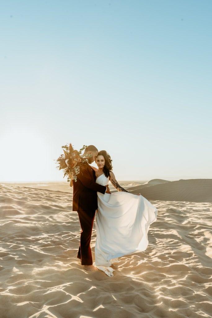 Bride's billowing wedding dress blowing in the desert breeze as her husband holds her at their desert elopement