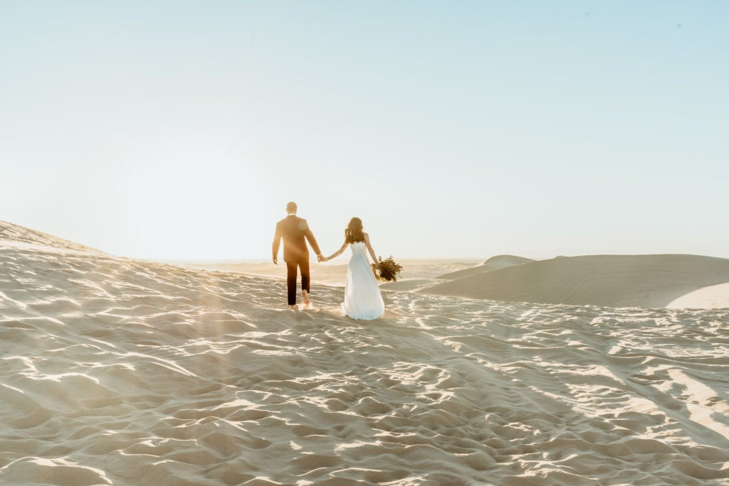 Couple walking up a large sand dune in wedding attire