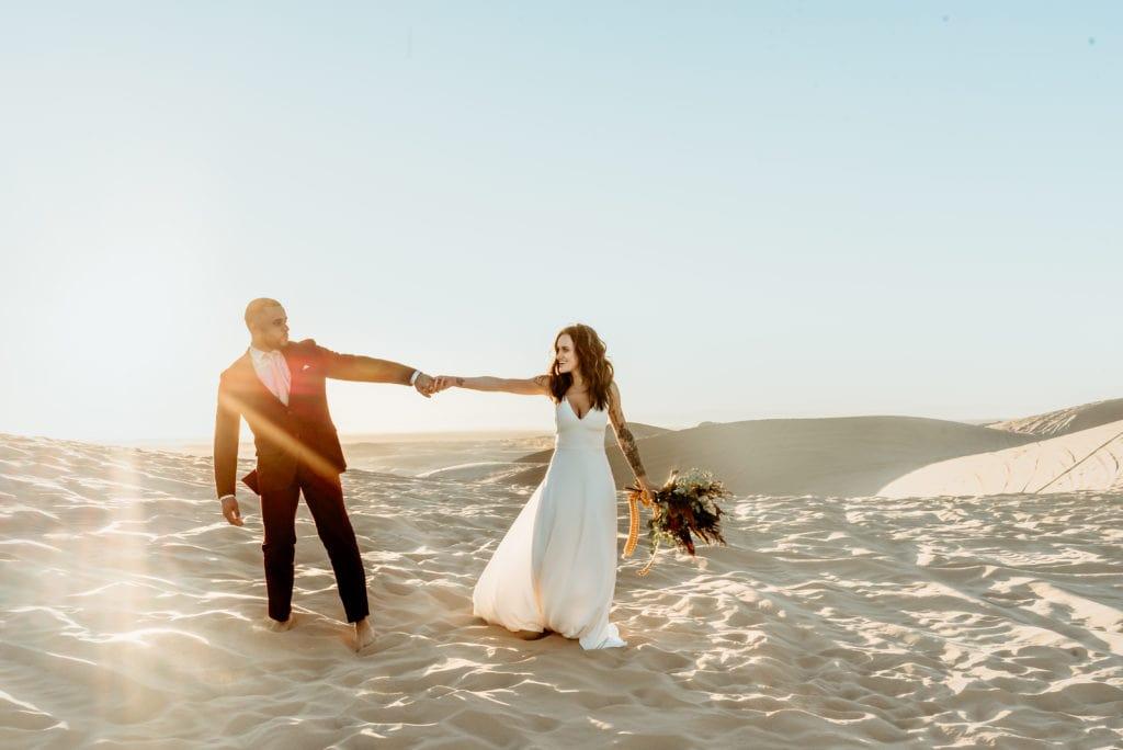 Elopement couple playfully walk hand in hand, barefoot, across the endless desert sand dunes