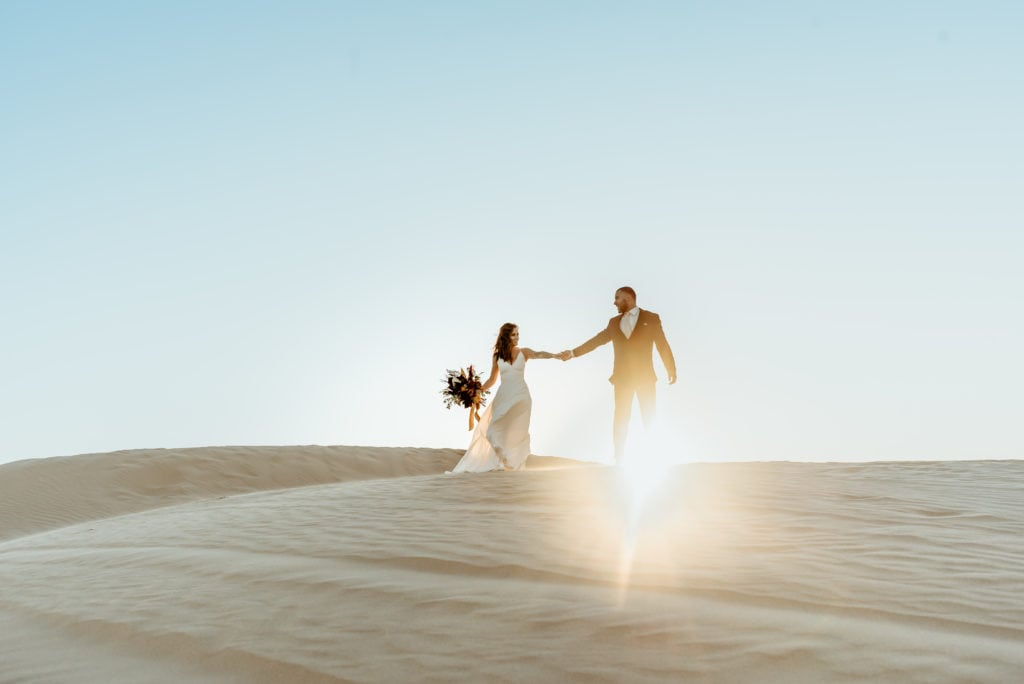 Elopement couple walking hand in hand down Glamis Sand Dunes as the sun sets behind them