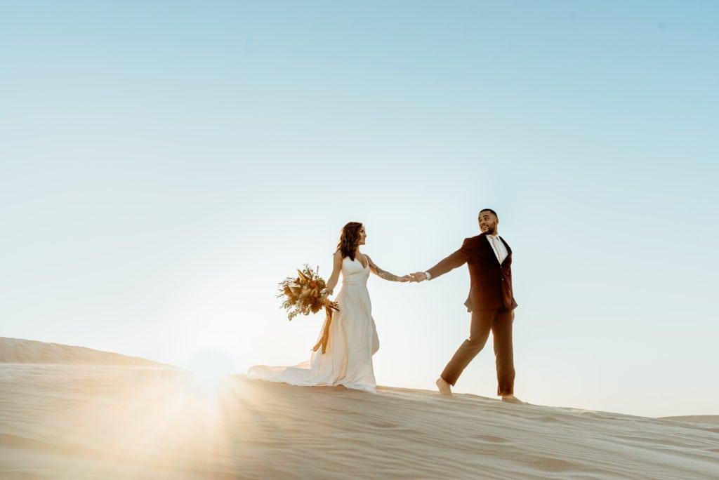 Groom leading his bride across the desert during their sand dune wedding