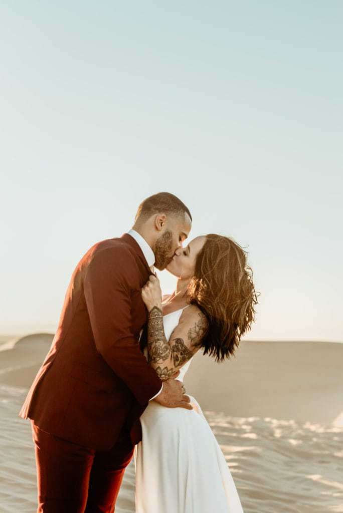 Bride grabbing her husband to her for a passionate kiss by his dark maroon suit