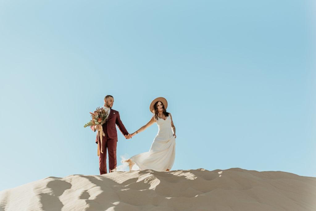 Couple wandering across the desert landscape at their sand dune elopement